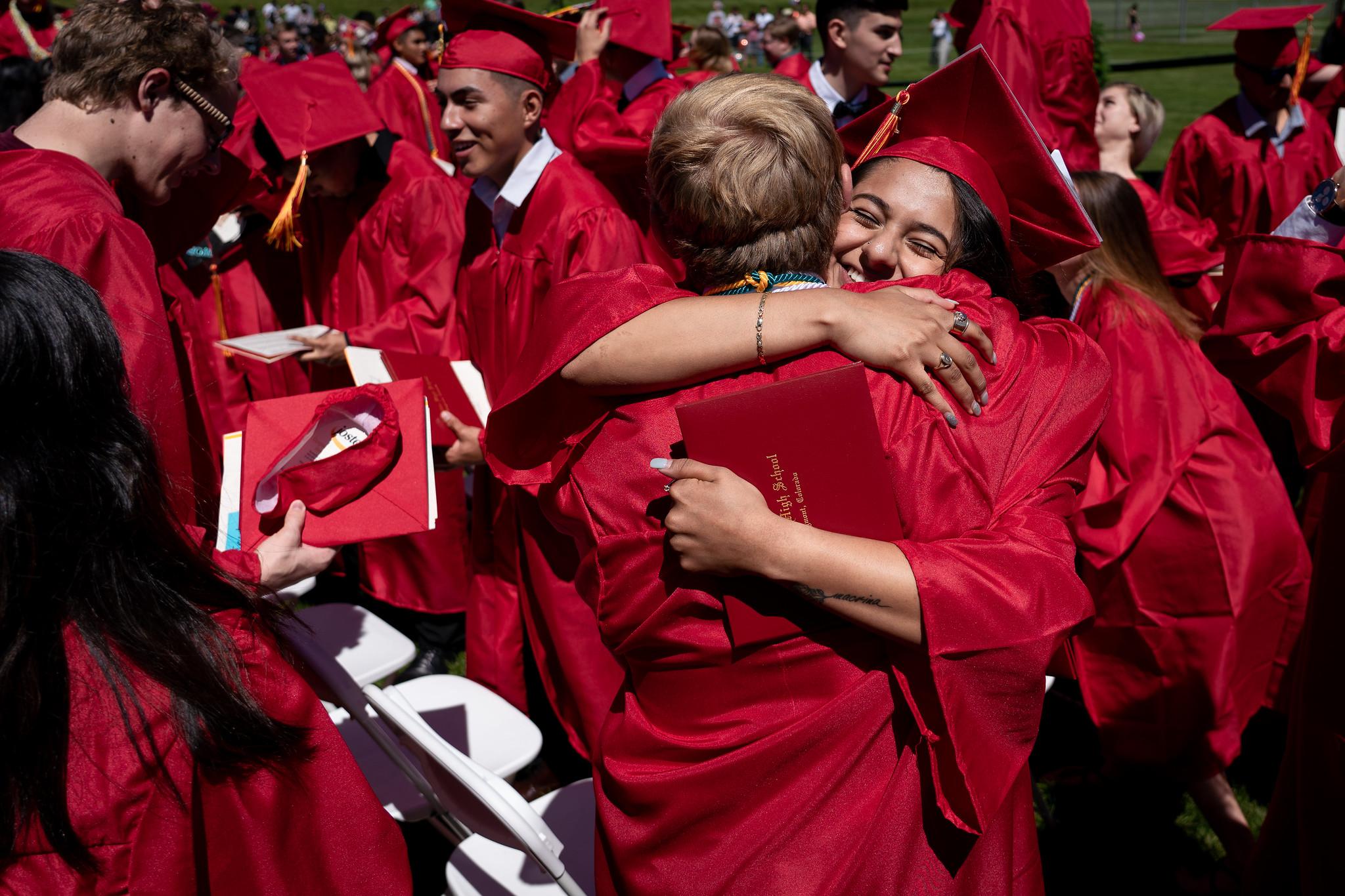 students hugging at graduation